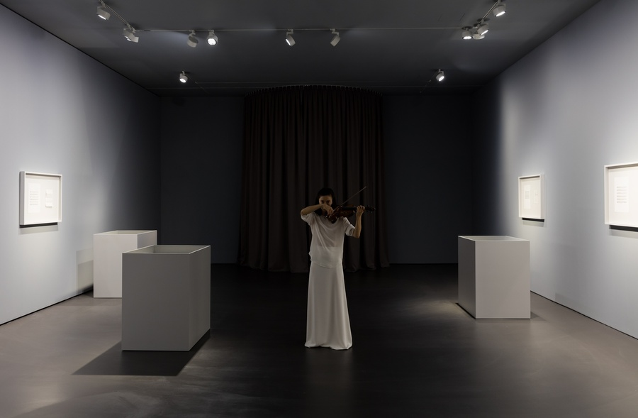 Ayumi Paul performing Ari Benjamin Meyers' score in the exhibition space, surrounded by twleve diptychs consisting of her personal objects paired with letter-scores.   Photo © Andrea Rossetti