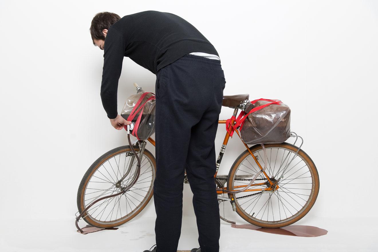 """Bastian Hoffmann, How to prepare a bike that cycles everyday in mud (Skulptur), aus der Tutorial Clip-Serie """"Today I want to show you..."""", 2011 – fortlaufend, Fahrrad, Kanister, Schläuche, Spanngurte, Wasser, Erde, Bild: ©Bastian Hoffmann"""